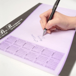 writing on a notepad designed with a calendar